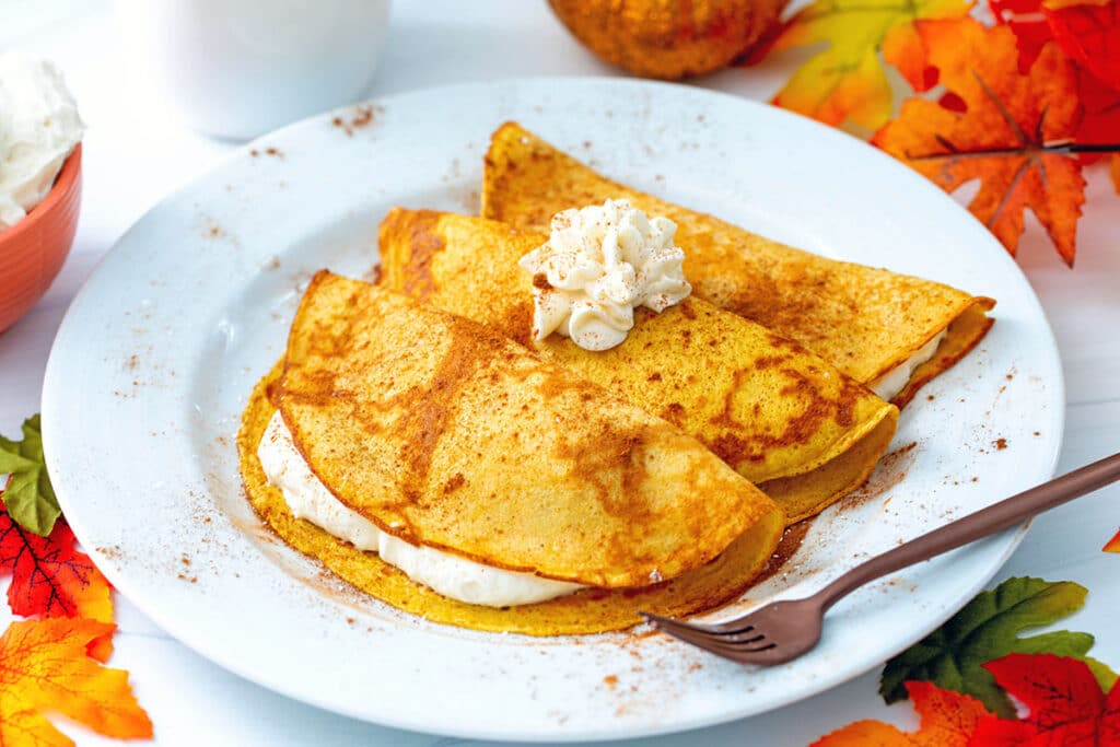 Landscape view of three pumpkin crepes on a white plate with maple cream cheese in and on crepes