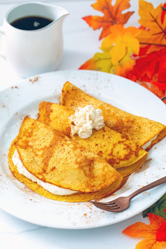 Head-on view of a plate with three pumpkin crepes filled and topped with maple cream cheese with fall leaves and a pitcher of maple syrup in the background