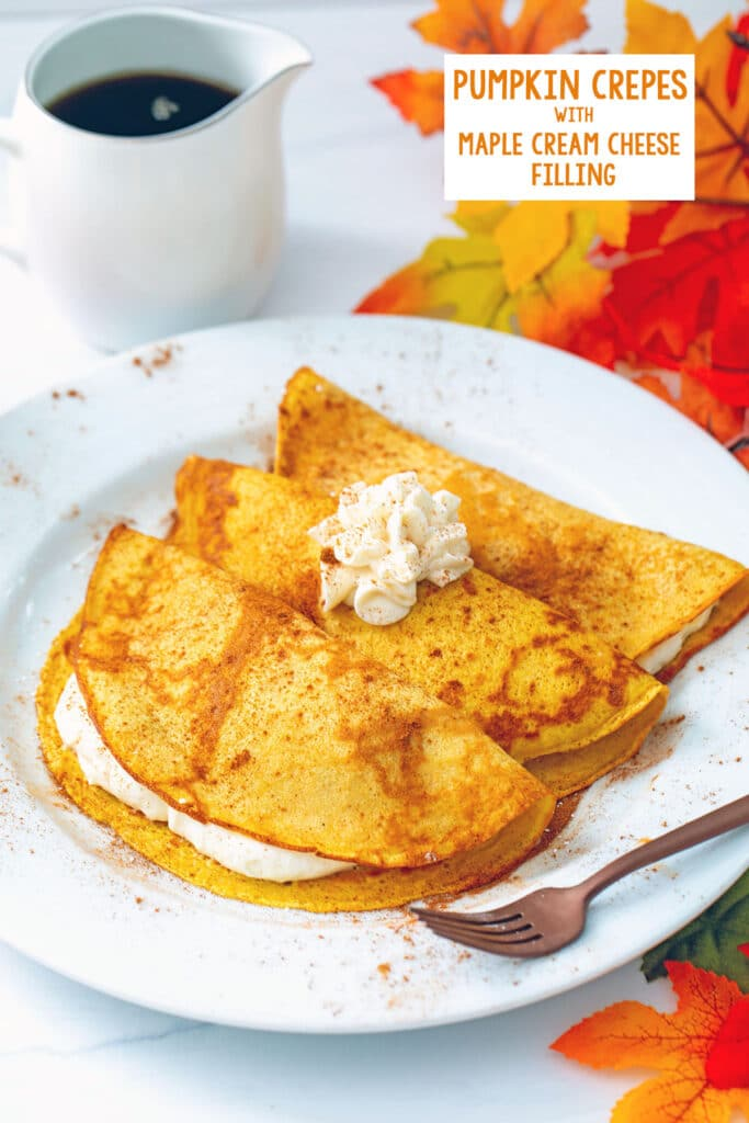 Head-on view of a plate with three pumpkin crepes filled and topped with maple cream cheese with fall leaves and a pitcher of maple syrup in the background and recipe title at top