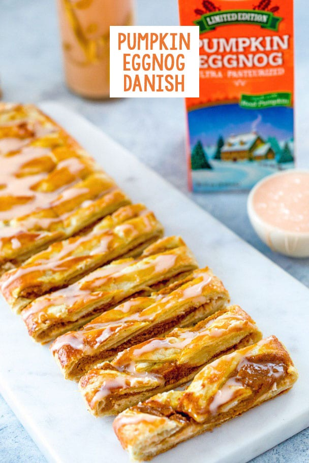 Overhead view of pumpkin eggnog danish with icing, sliced on a marble platter with carton and glass of pumpkin eggnog in the background, bowl of pumpkin eggnog icing, and recipe title at top of image