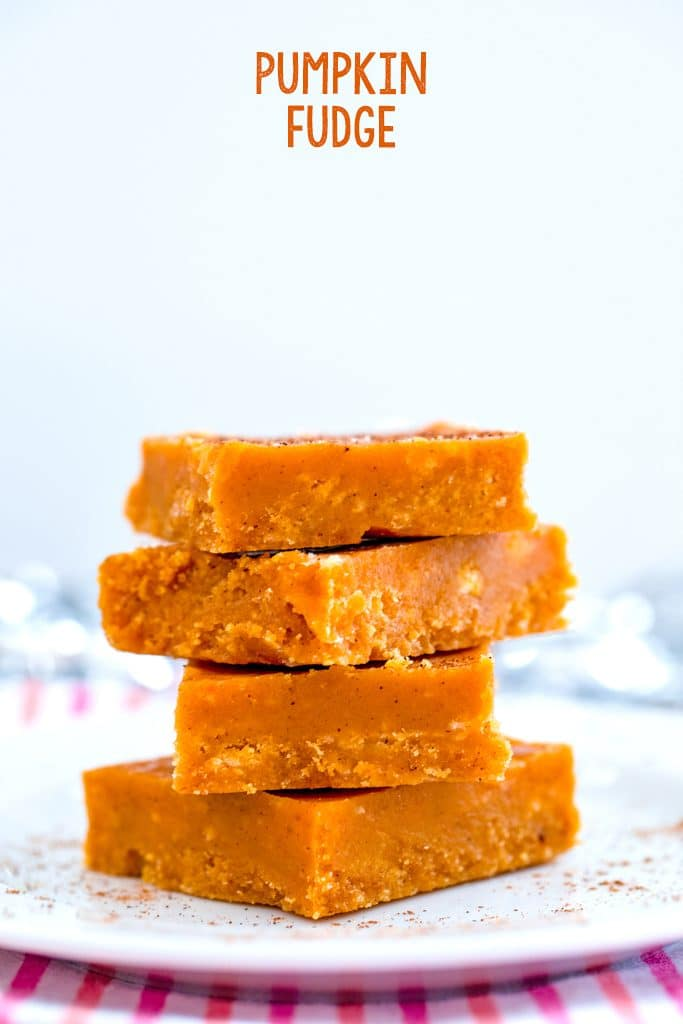 """Head-on closeup view of four squares of pumpkin fudge stacked on a white plate with """"Pumpkin """"Fudge"""" at the top of the image"""
