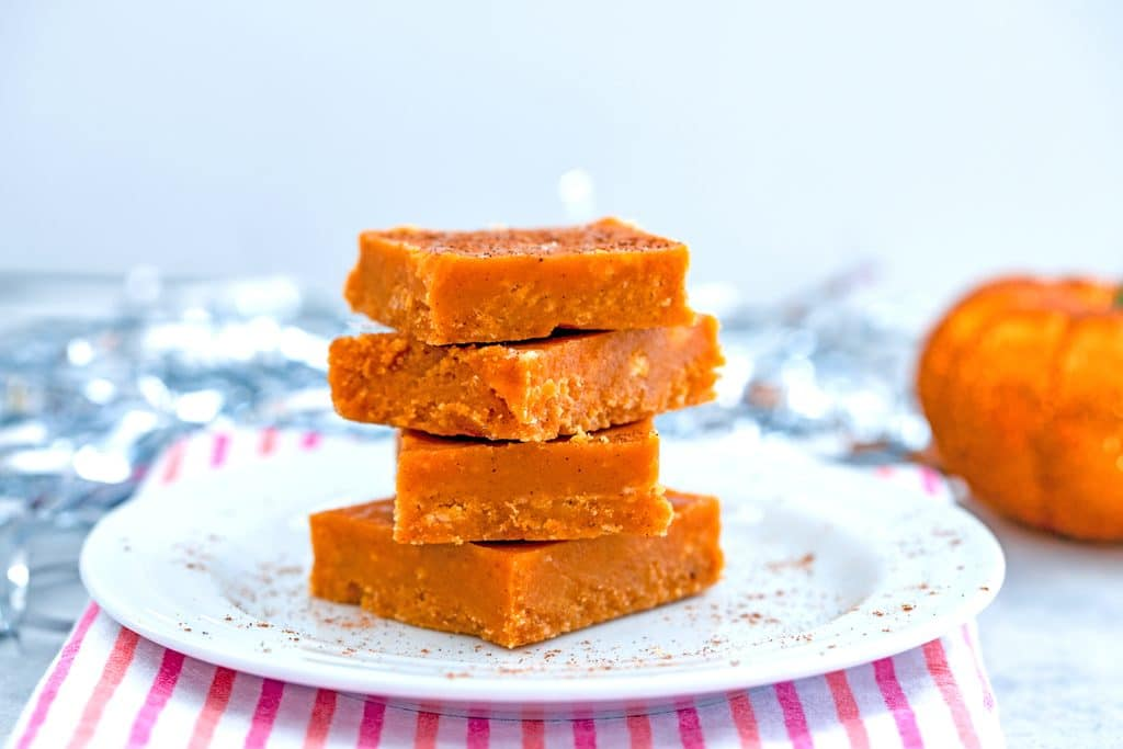 Landscape view of four squares of pumpkin fudge stacked on a white plate with pumpkin pie spice sprinkled around, silver confetti, and a glittery orange pumpkin in the background