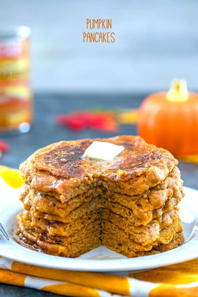 "Head-on view of white plate with stack of pumpkin pancakes with with a wedge cut out and a pat of butter on top with ""Pumpkin Pancakes"" text at top"