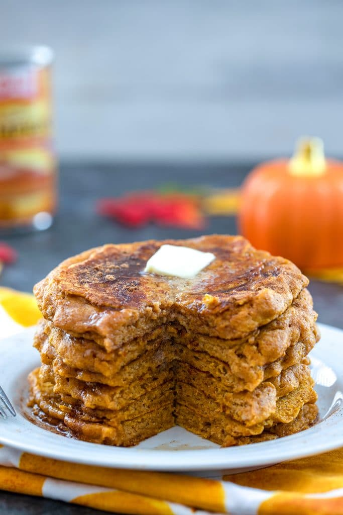 Head-on view of white plate with stack of pumpkin pancakes with with a wedge cut out and a pat of butter on top