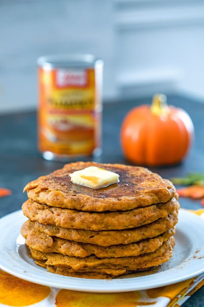 Head-on view of a stack of pumpkin pancakes with a pat of butter on top and a can of pumpkin puree and pumpkin in the background