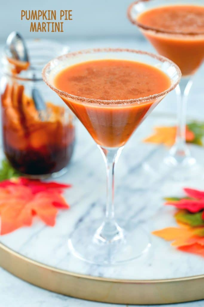 "Head-on close-up view of a pumpkin pie martini on a marble surface with a second one, maple leaves, and a jar of caramel sauce in the background and ""Pumpkin Pie Martini"" text at the top"