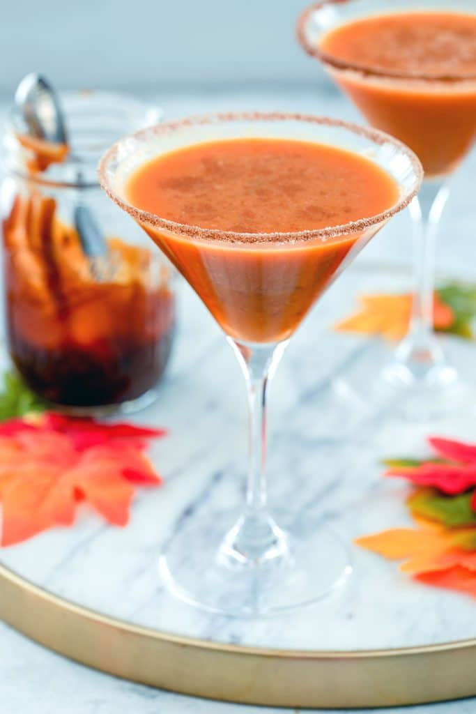 Head-on close-up view of a pumpkin pie martini on a marble surface with a second one, maple leaves, and a jar of caramel sauce in the background