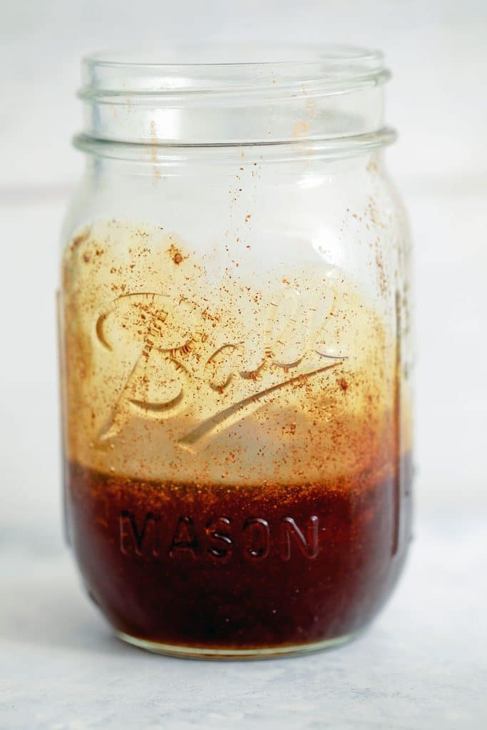 Head-on view of mason jar filled with pumpkin caramel syrup
