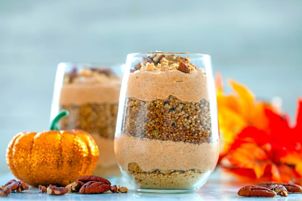 Landscape closeup head-on view of pumpkin quinoa parfait in a glass surrounded by crushed pecans, glitter pumpkin, fall leaves, and second parfait