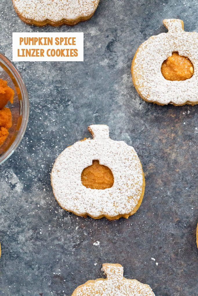 Overhead view of multiple pumpkin spice linzer cookies topped with confectioners' sugar on a dark background with recipe title at top