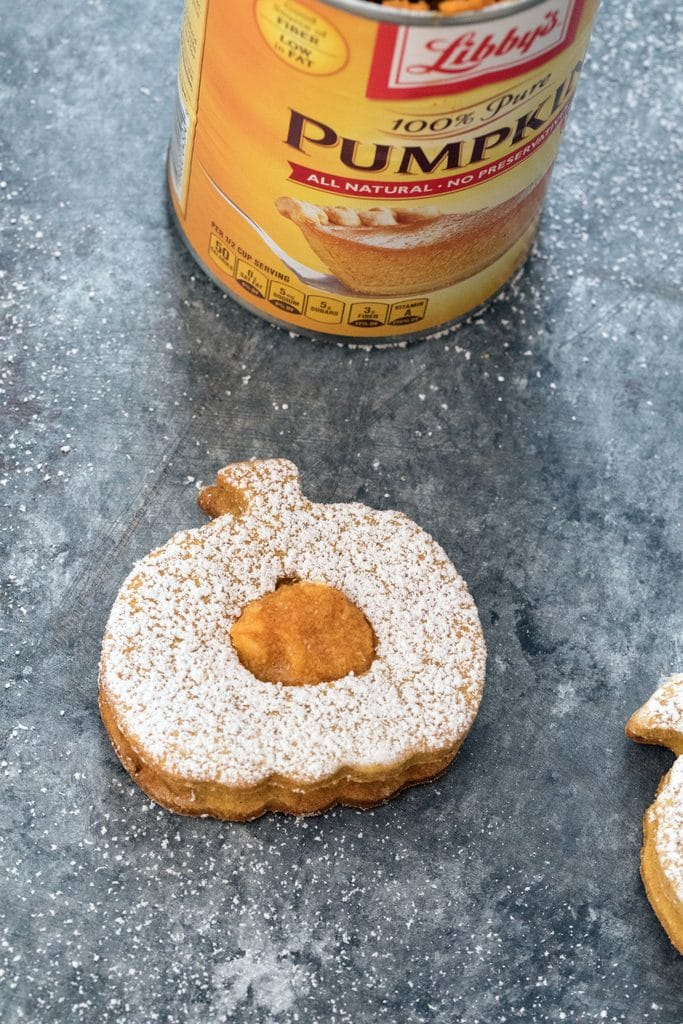 Overhead view of a pumpkin spice linzer cookie with confectioners' sugar and pumpkin filling on a dark surface with can of pumpkin puree in the background