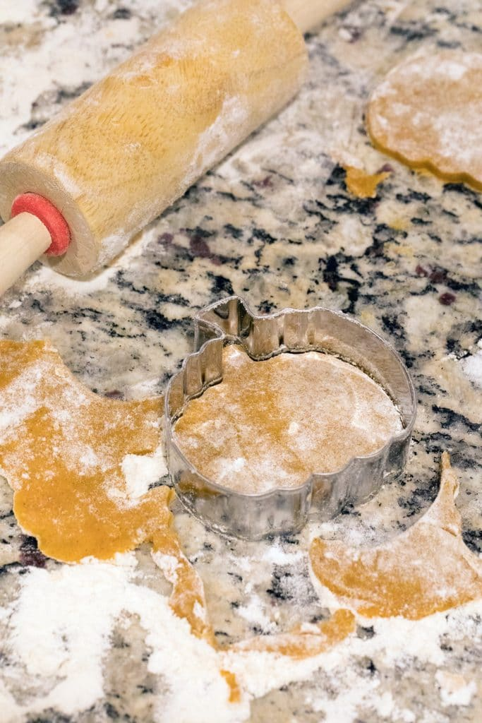 Overhead view of pumpkin spice linzer cookie dough on counter with pumpkin shaped cookie cutter and mini rolling pin