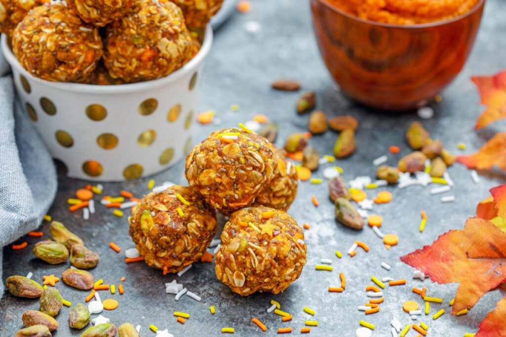 Landscape view of pumpkin spice energy balls with more energy bites and pumpkin puree in background with ingredients and fall leaves all around