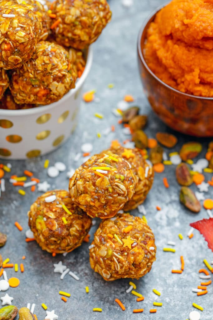 Overhead view of pumpkin spice pistachio energy balls with more energy bites and pumpkin puree in background and ingredients all around