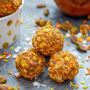 Head-on closeup view of pumpkin spice pistachio energy balls with pumpkin puree and more energy bites in background with ingredients all around