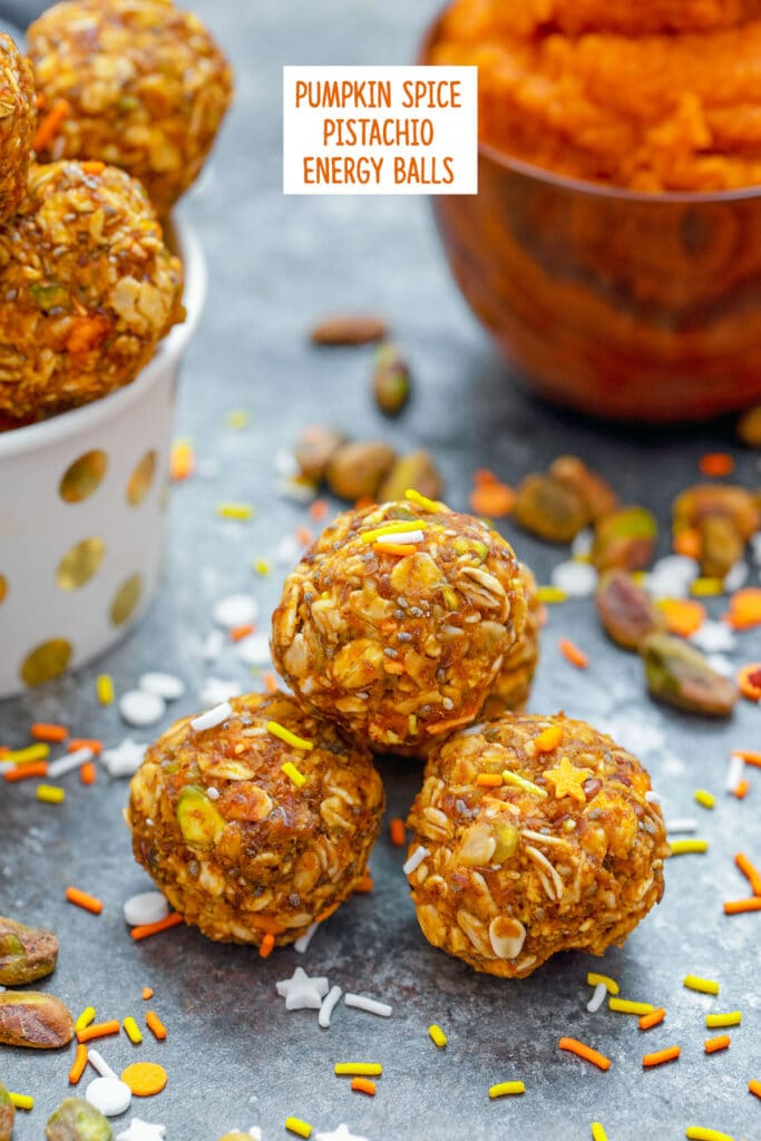 Head-on closeup view of pumpkin spice pistachio energy balls with pumpkin puree and more energy bites in background with ingredients all around and recipe title at top