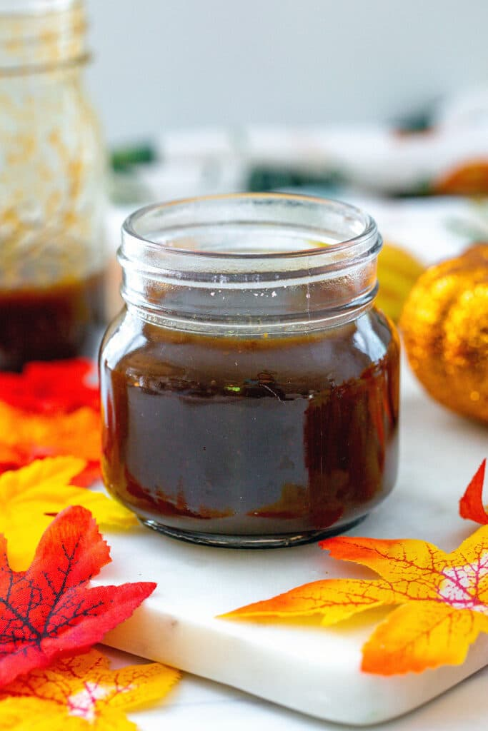 Head-on closeup view of a small jar of pumpkin spice syrup with fall leaves and large jar of syrup in background