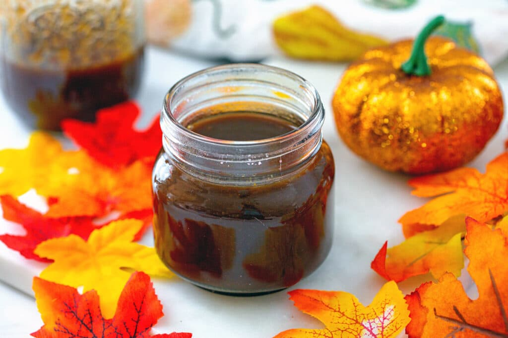Landscape overhead view of pumpkin spice syrup in a small mason jar with fall leaves, glittery pumpkin, and second mason jar in background