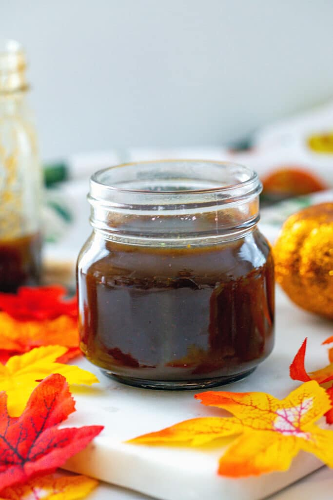 Head-on view of pumpkin spice syrup in a small mason jar with fall leaves all around