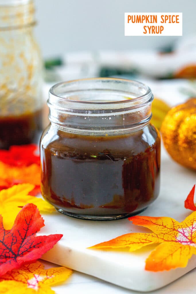 Head-on view of a small jar of pumpkin spice syrup with fall leaves and large jar of syrup in background and recipe title at top