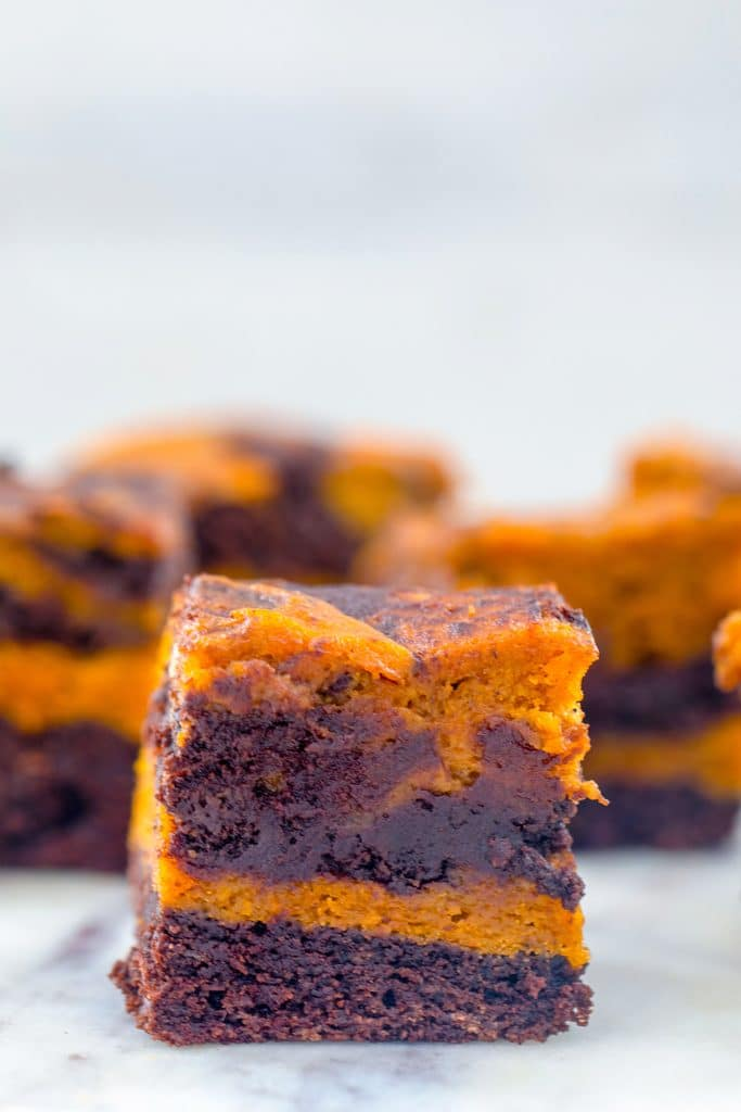 Head-on closeup view of a pumpkin swirl brownie on a marble surface with more brownies in the background
