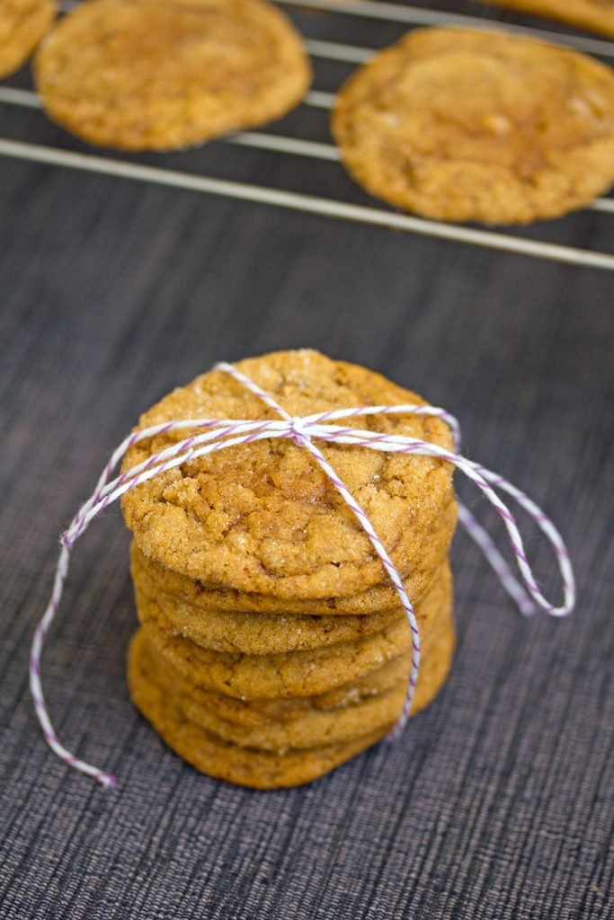 Overhead view of a stack of pumpkin gingersnap cookies tied up with bakers twine with a rack with more cookies in the background