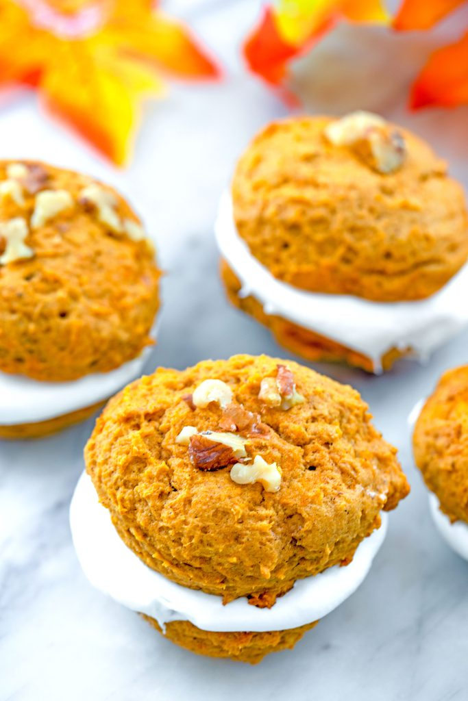 Overhead view of multiple pumpkin whoopie pies topped with walnuts on a marble surface with fall leaves in the background