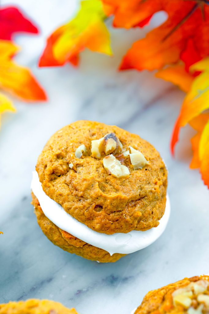 Head-on view of a pumpkin whoopie pie filled with marshmallow cream and topped with walnuts on a marble surface with colorful fall leaves in the background