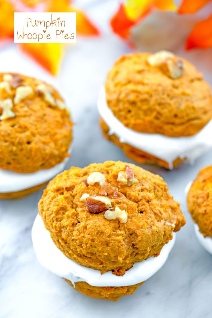 Overhead view of multiple pumpkin whoopie pies topped with walnuts on a marble surface with fall leaves in the background and recipe title at top