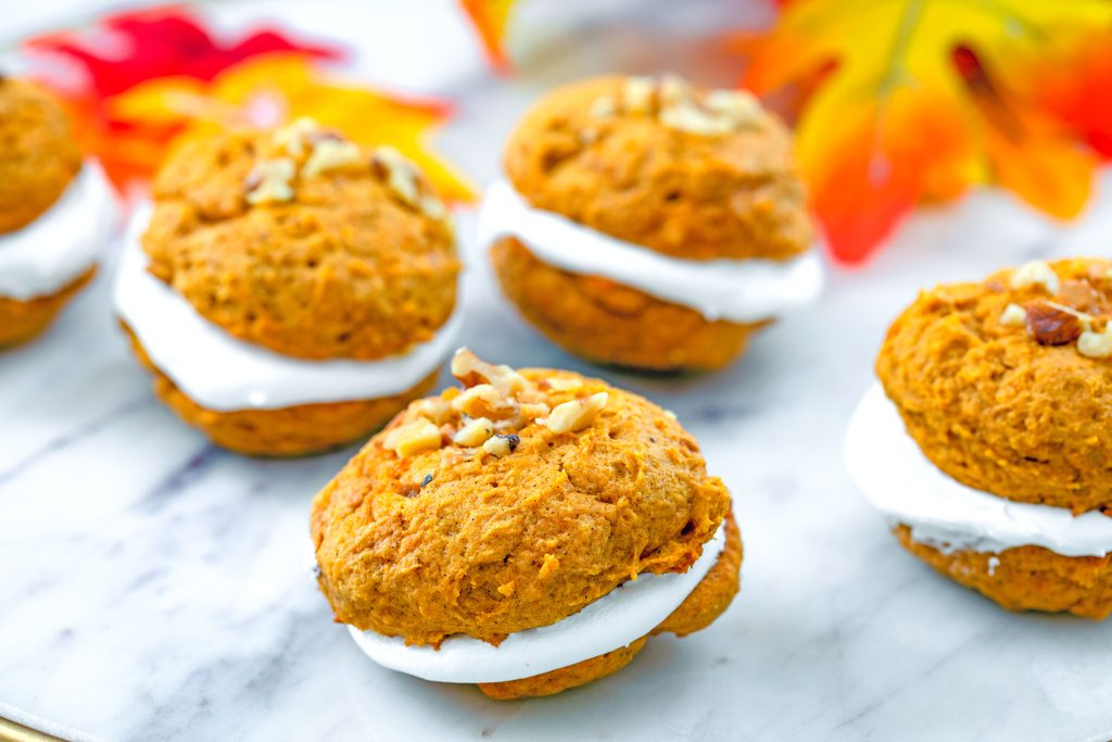 Landscape head-on view of multiple pumpkin whoopie pies topped with walnuts on a marble tray with colorful fall leaves in the background