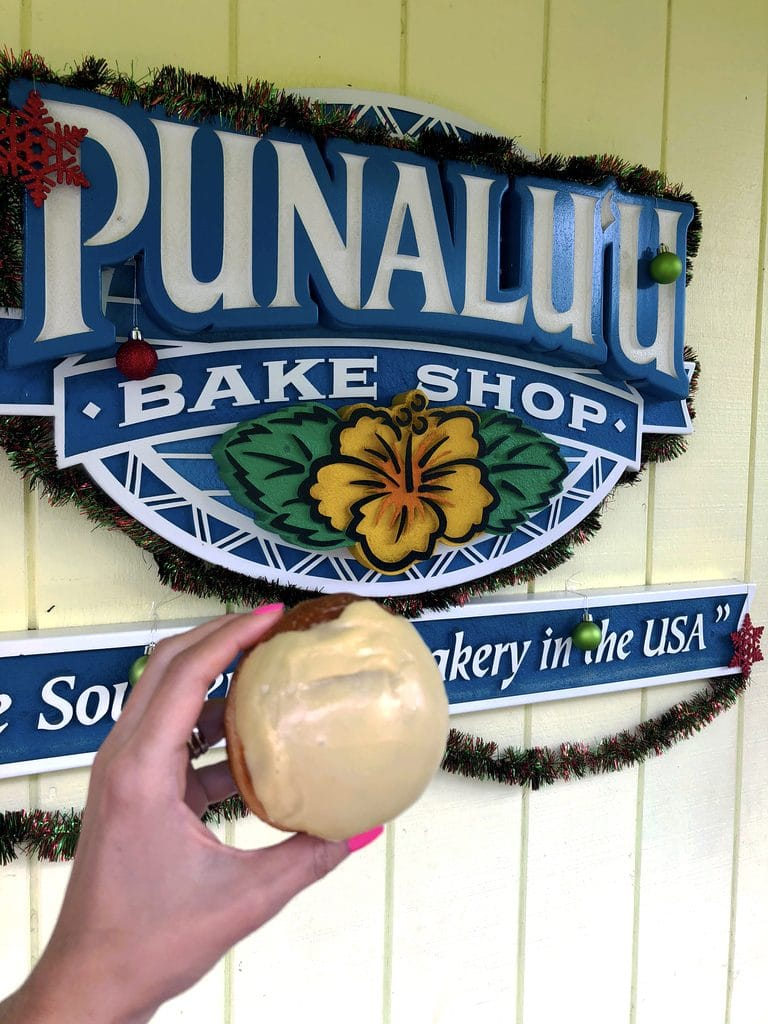 Passionfruit malasada in front of Punalu'u Bake Shop sign, the southernmost bakery in the United States on the Big Island of Hawaii