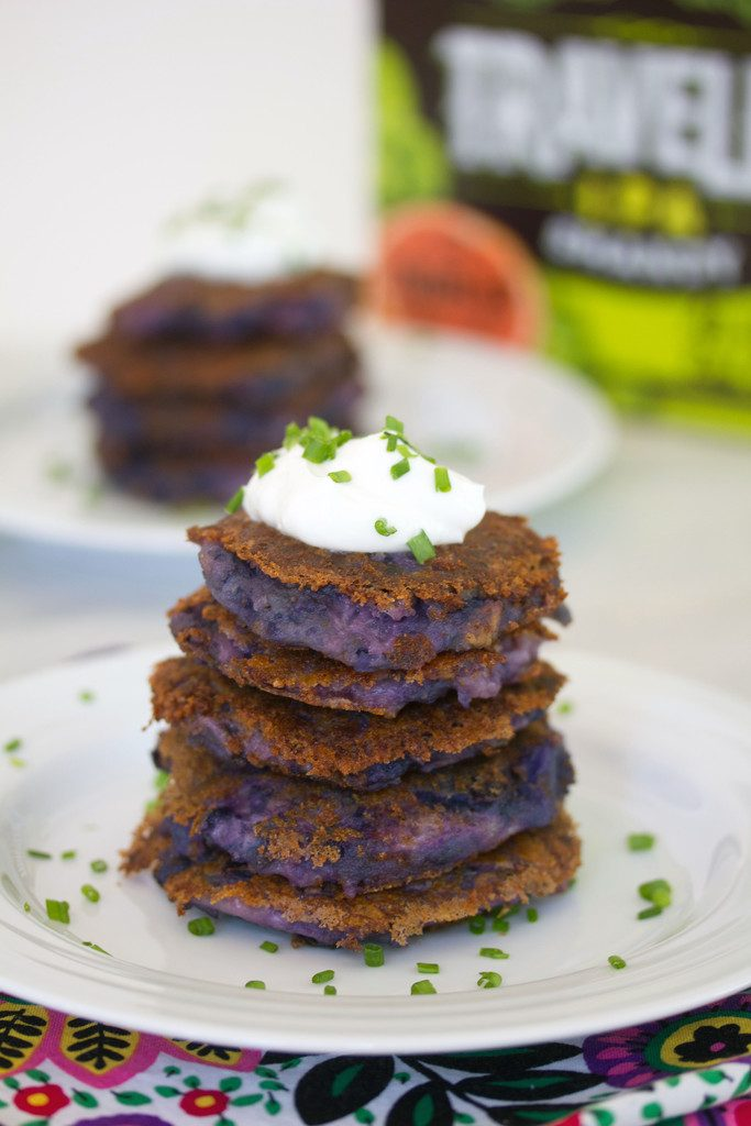 Head-on view of purple mashed potato pancakes in a stack and topped with Greek yogurt and chives with second plate of potato pancakes and box of beer in the background