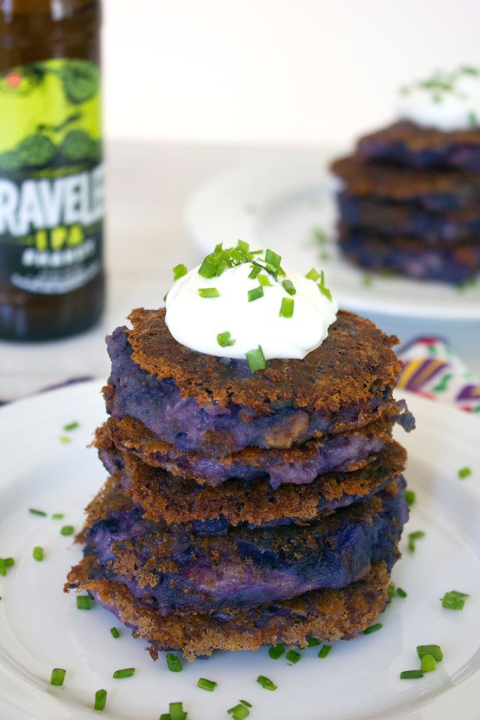 Head-on closeup view of a stack of purple mashed potato pancakes with garlic and pancetta topped with Greek yogurt and chives with a bottle of beer and more potato pancakes in the background