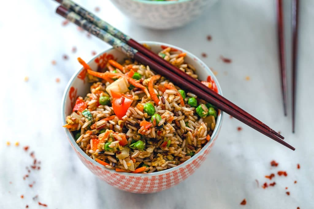 Landscape view of a bowl of quick vegetable fried brown rice with chopsticks balanced on top and red hot pepper flakes scattered around