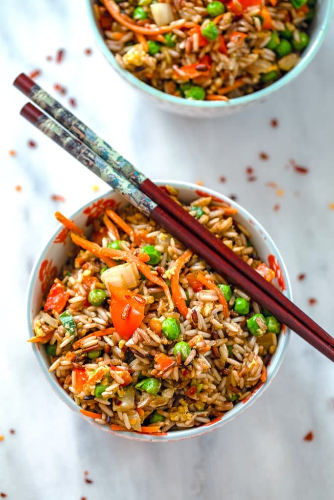 Overhead view of bowl of quick vegetable fried brown rice with chopsticks balancing on top and a second bowl in the background with red hot pepper flakes scattered around