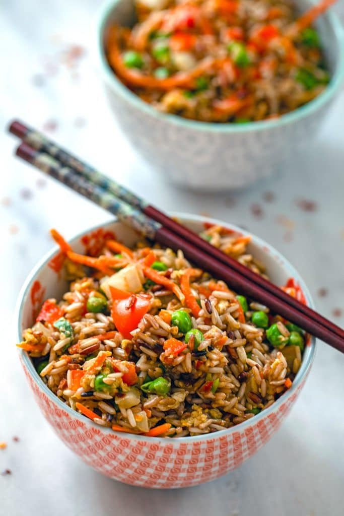Head-on view of a bowl of quick vegetable fried brown rice with chopsticks balancing on it, a second bowl of rice in the background