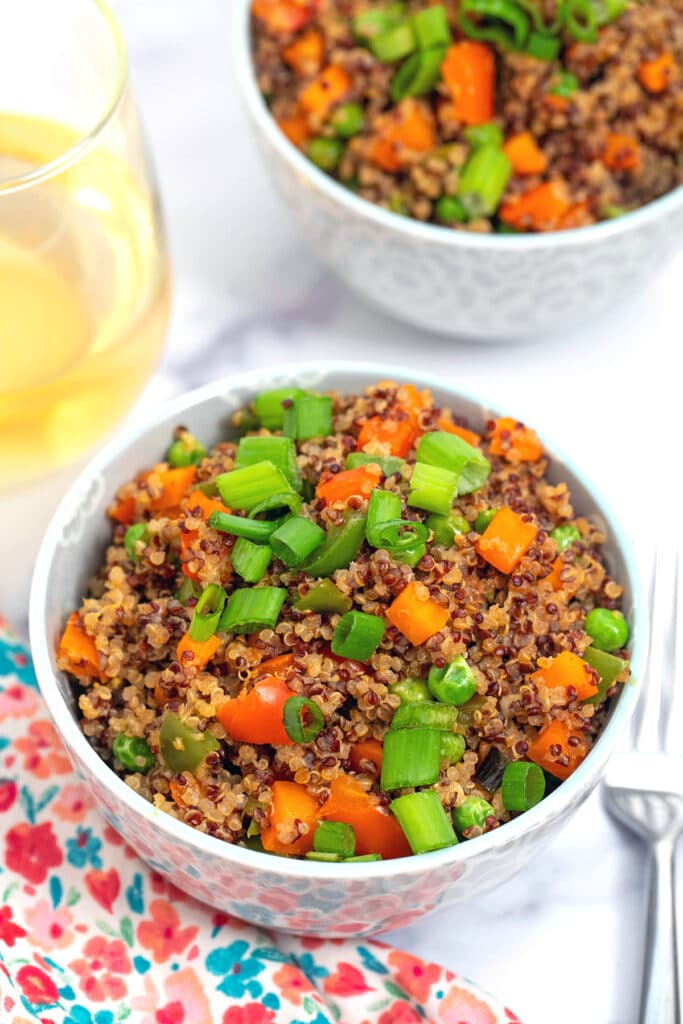 Overhead view of a bowl of quinoa fried rice with red and white quinoa, red and green peppers, carrots, and scallions, with second bowl and glass of white wine in background