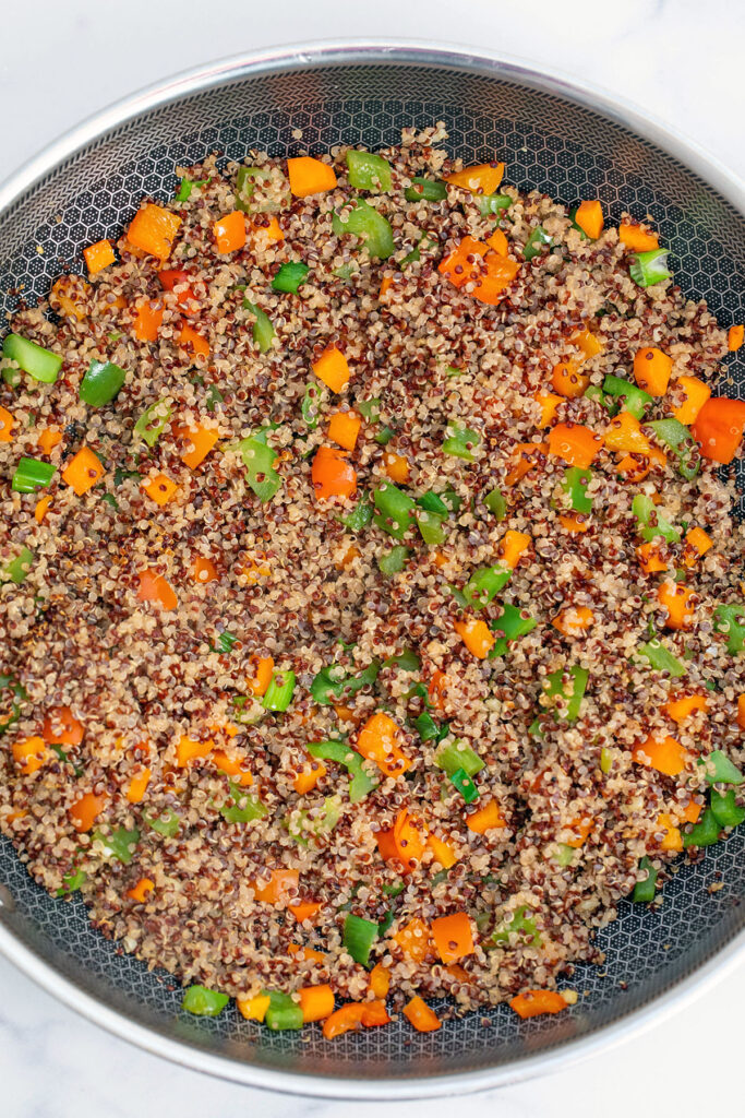 Overhead view of large wok with red and white quinoa and red and green peppers, scallions, and carrots
