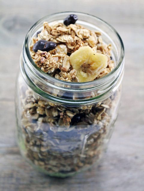 Mason jar filled to the top with quinoa granola with chocolate pomegranate arils and banana chips