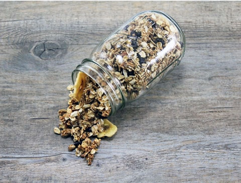 Landscape photo of mason jar on its side and quinoa granola with chocolate pomegranate arils and banana chips spilling out