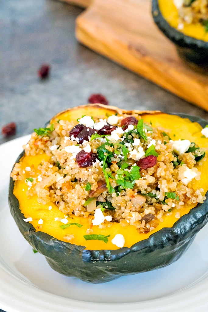 Head-on view from the side of a half an acorn squash stuffed with quinoa, mushrooms, spinach, dried cranberries, and feta