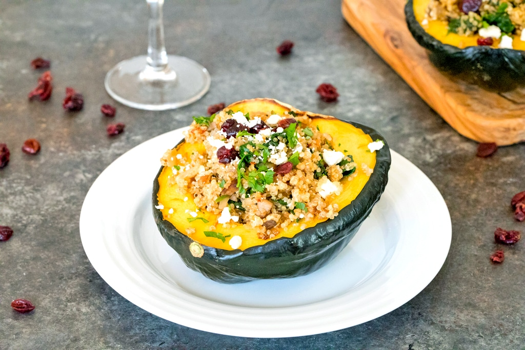 Landscape view of a white plate with half an acorn squash with quinoa, spinach, cranberries, and feta with wine glass and cutting board with second stuffed squash in the background and dried cranberries all around