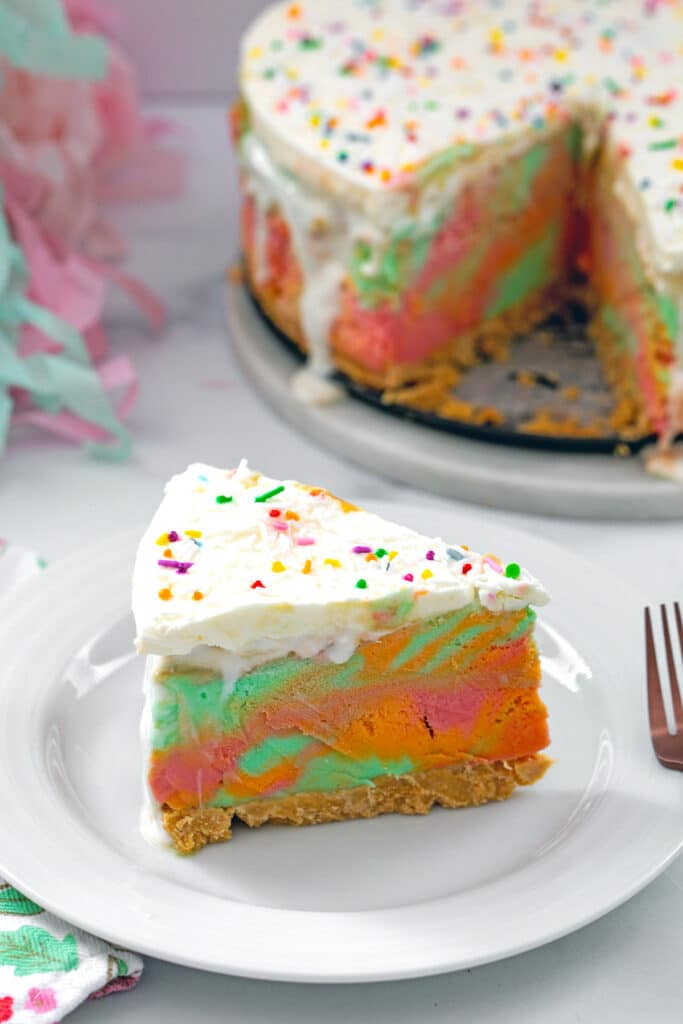 Head-on view of a slice of rainbow sherbet cake on a plate with rest of whole cake in background