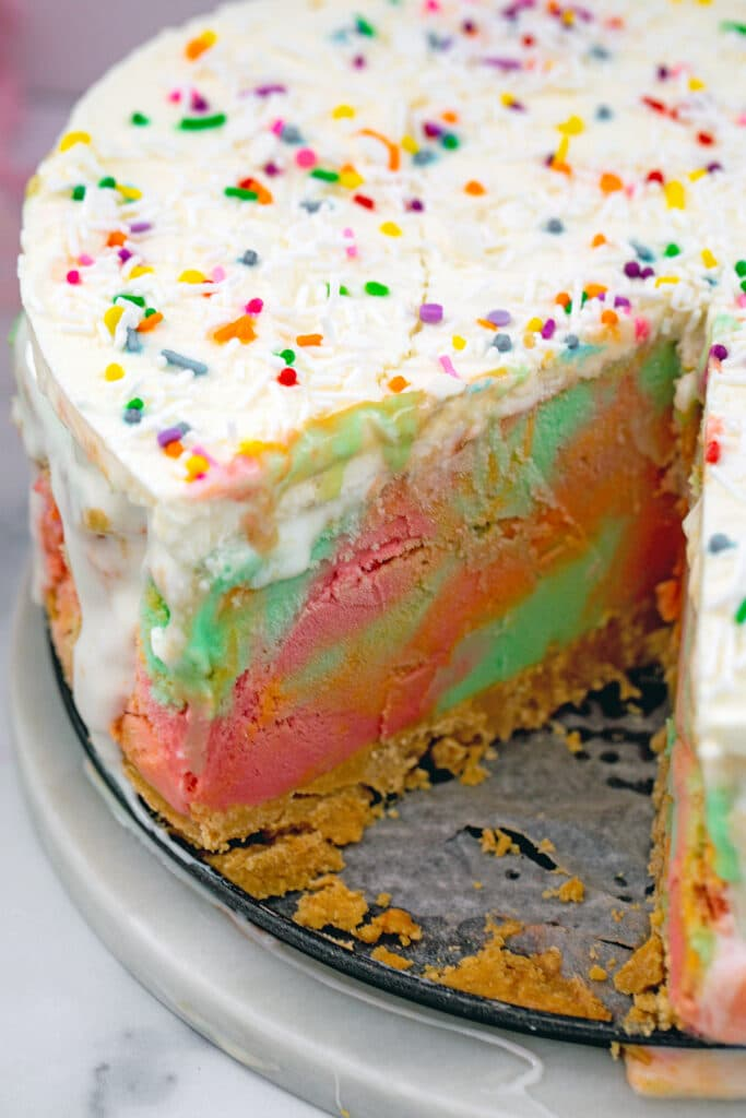 Rainbow sherbet ice cream cake with a slice removed from it