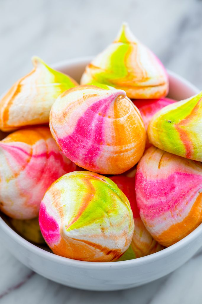 Head-on view of a white bowl filled with pink, orange, and green rainbow sherbet meringues
