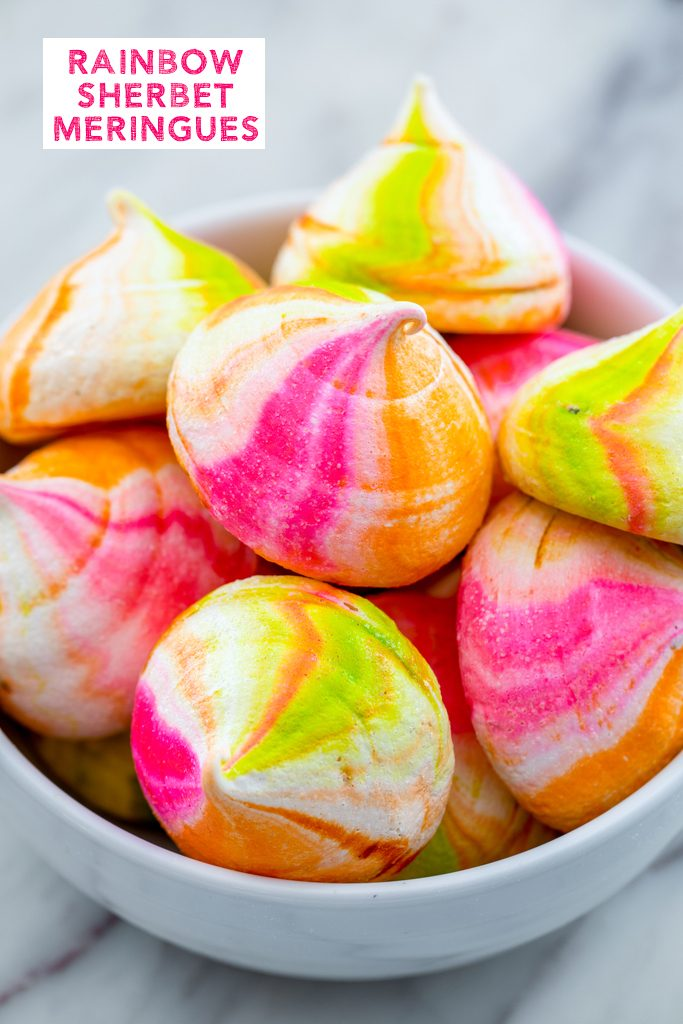 Head-on view of a white bowl filled with pink, orange, and green rainbow sherbet meringues with recipe title at top