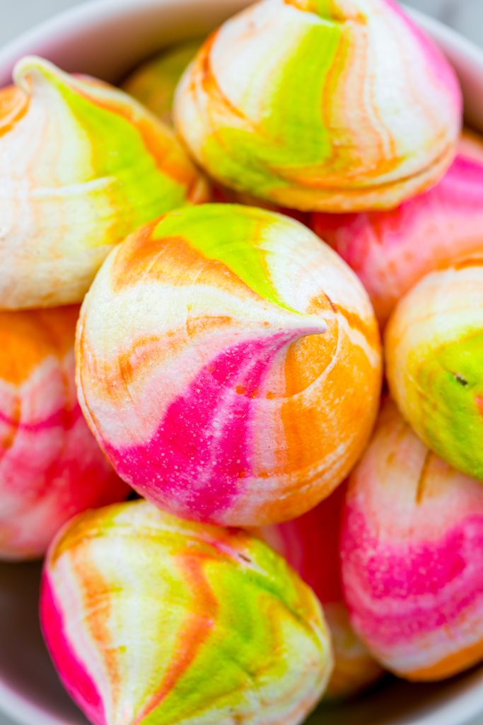 Overhead view of a bowl of pink, green, and orange rainbow sherbet meringues