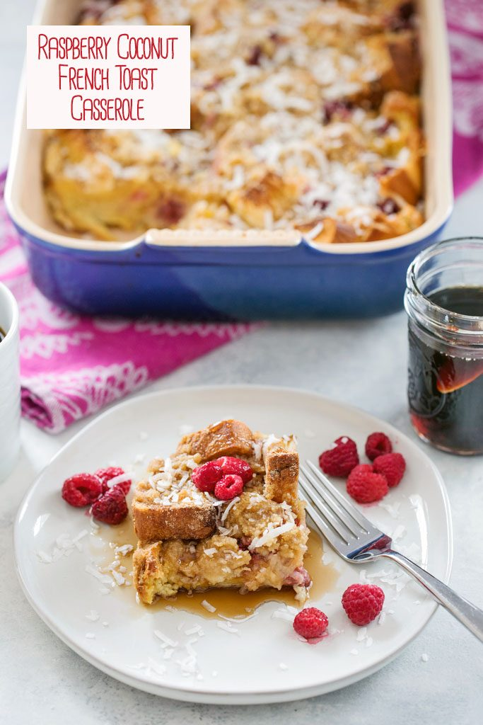 Overhead view of a plate with a serving of raspberry coconut french toast casserole with the baking dish in the background, along with a jar of maple syrup with recipe title at top