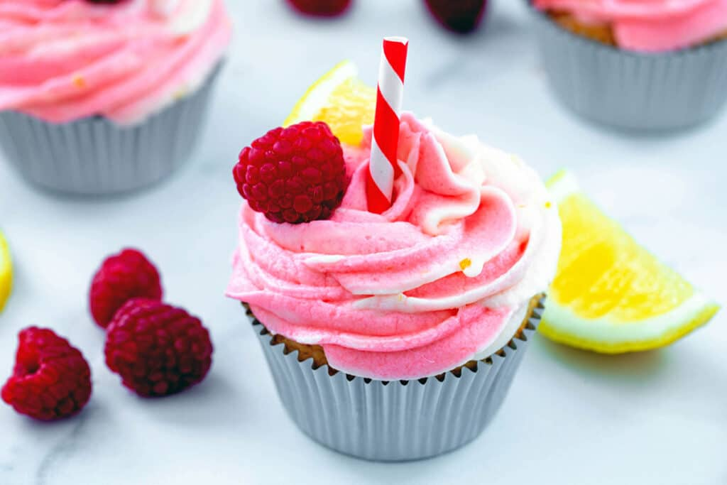 Landscape overhead view of a raspberry lemonade cupcake with raspberries and lemon wedges and more cupcakes in background