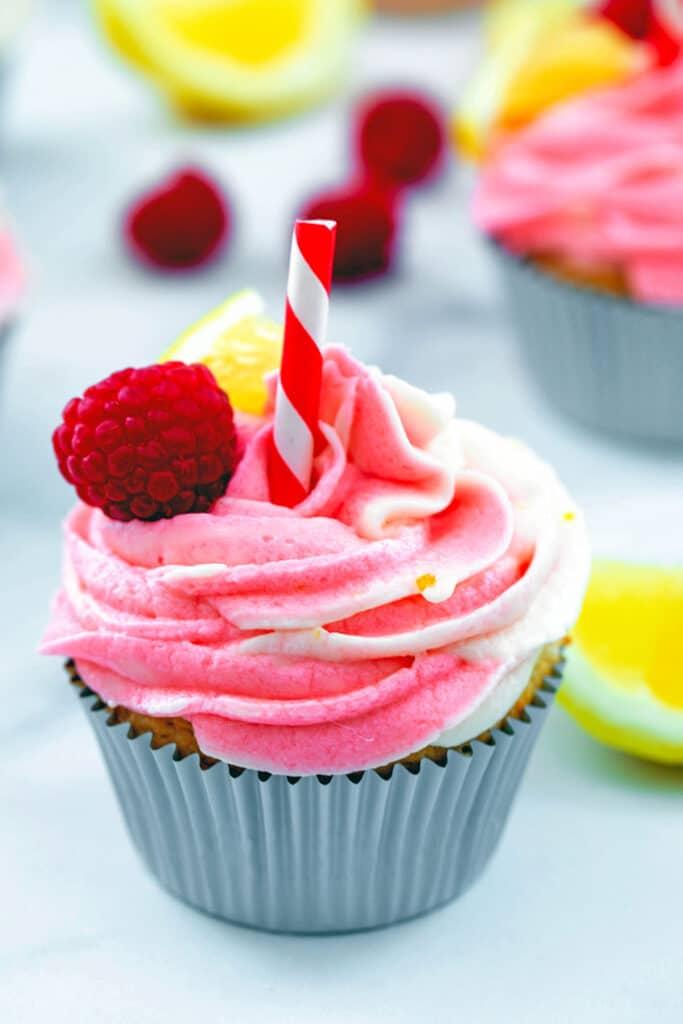 Head-on view of raspberry lemonade cupcake with raspberries and lemon wedges in background